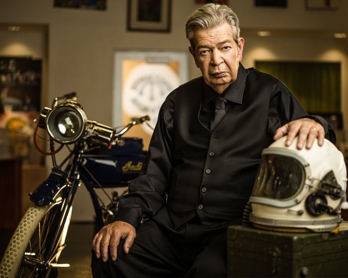 Richard Harrison is posing on a chair resting his left hand on a motorcycle helmet. In the background rests a classic motorbike. Richard is facing straight to the camera. He looks dashing in his all-black apparel.