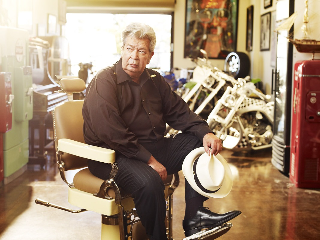 Richard Harrison is sitting on a chair looking away from the camera. He is wearing a black jacket and a black lining pant. There are few motorbikes in the background. A bright light can be seen in the top left corner of the picture.