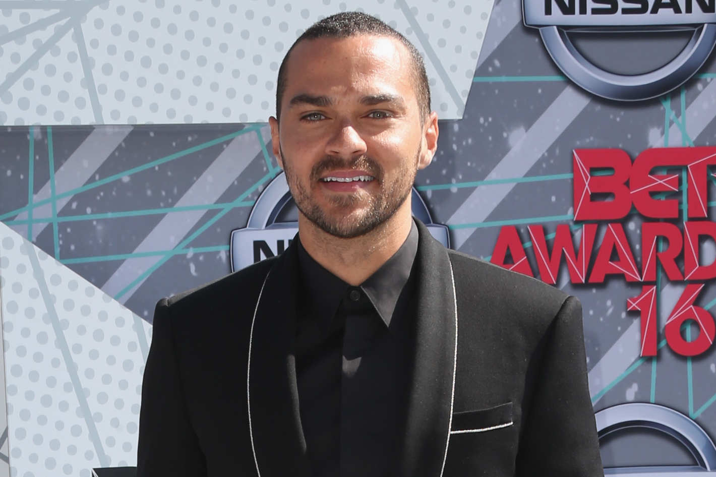 Jesse Williams smiling for a picture wearing a black suit