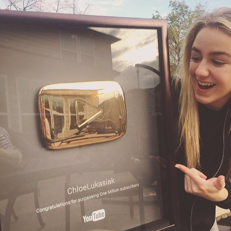 Chloe Lukasiak pointing at her framed YouTube Gold Play Button