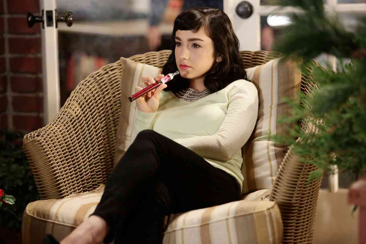 Molly Ephraim is sitting in a bamboo chair holding a pipe in her right hand