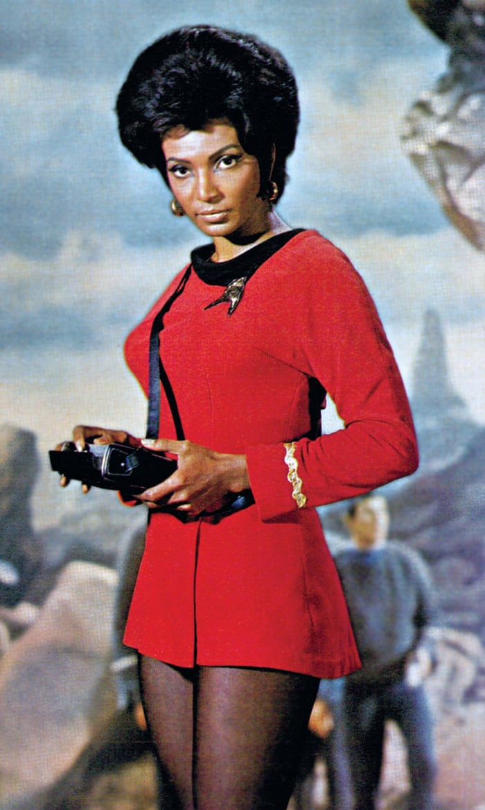Nichelle Nichols in Star Trek dress holding fancy remote control in the movie