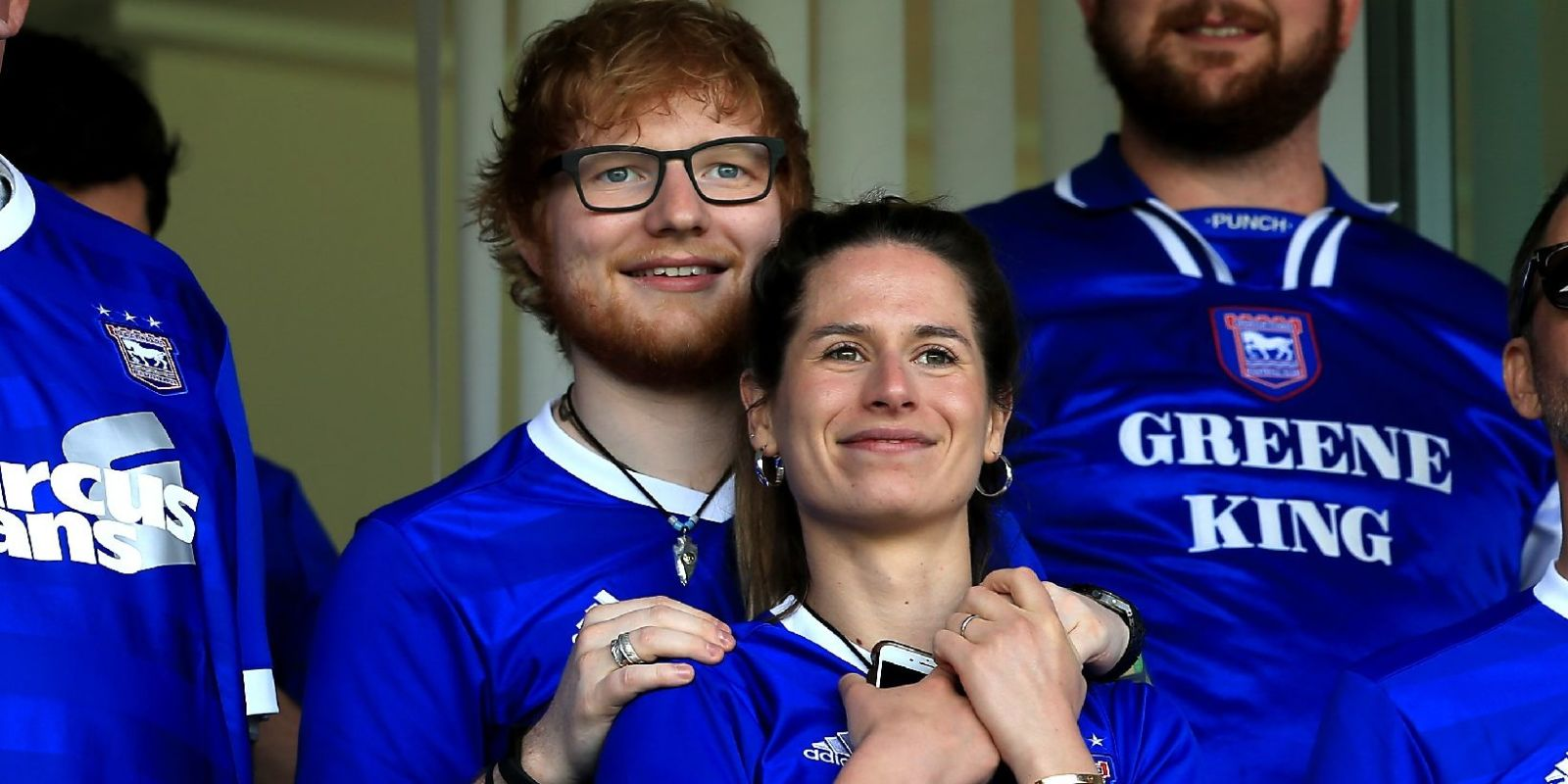Ed Sheeran and his fiance Cherry Seaborn at a game wearing a blue jersey