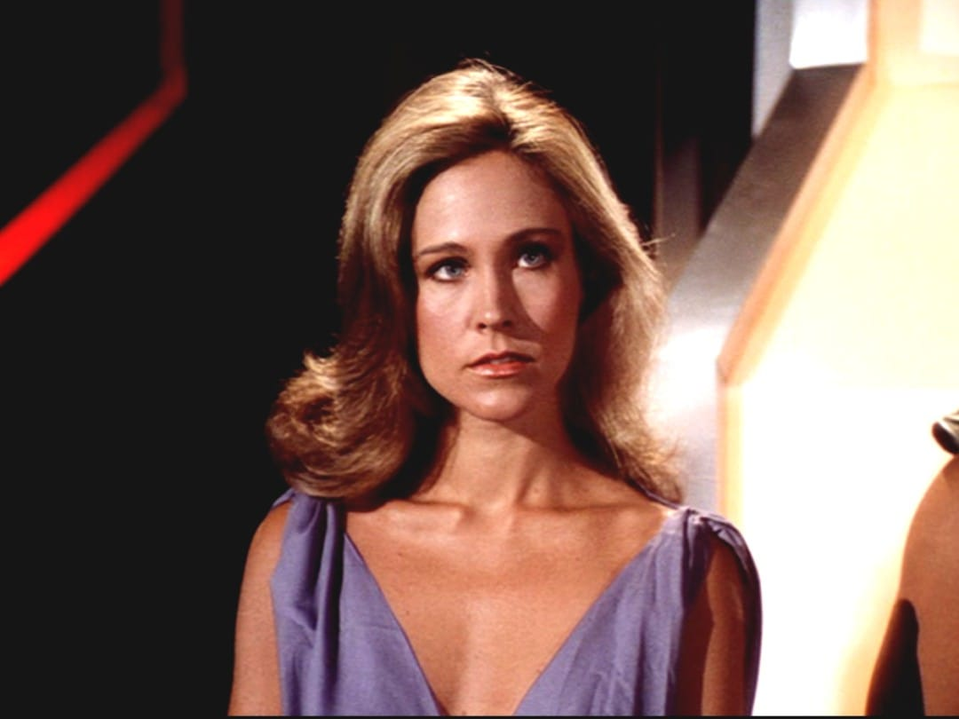 Erin Gray looking somewhere in a scene of a movie