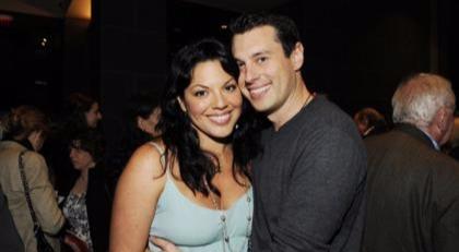 Sara Ramirez with his husband Ryan DeBolt. Both of them are smiling at the camera.