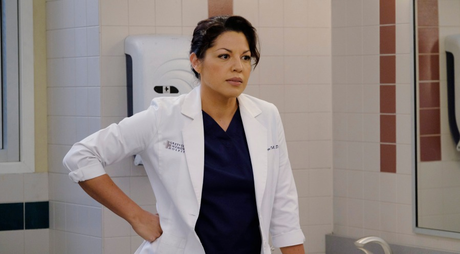 Sara Ramirez portraying Callie Torres, she's wearing a doctor's coat and has her hand on her waist
