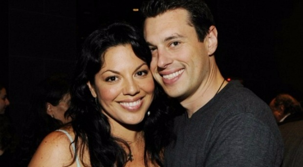 Sara Ramirez and Ryan DeBolt smiling for the photo, there are a few people behind them