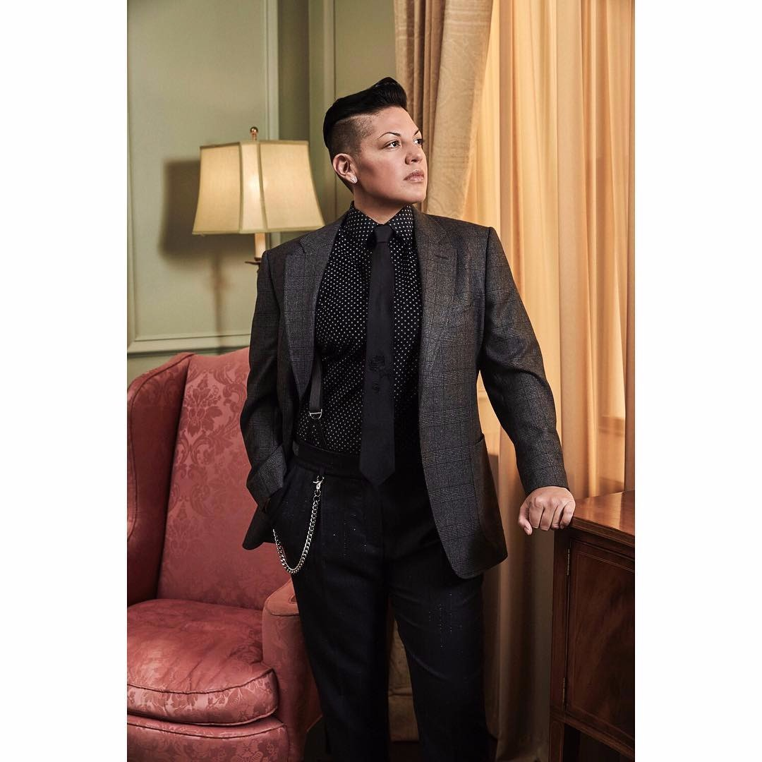 Sara Ramirez is dressed in a black suit. She has undercut hairstyle.