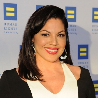 Sara Ramirez looks beautiful wearing white T-shirt and black outer. She is smiling for the camera. She is openly bisexual