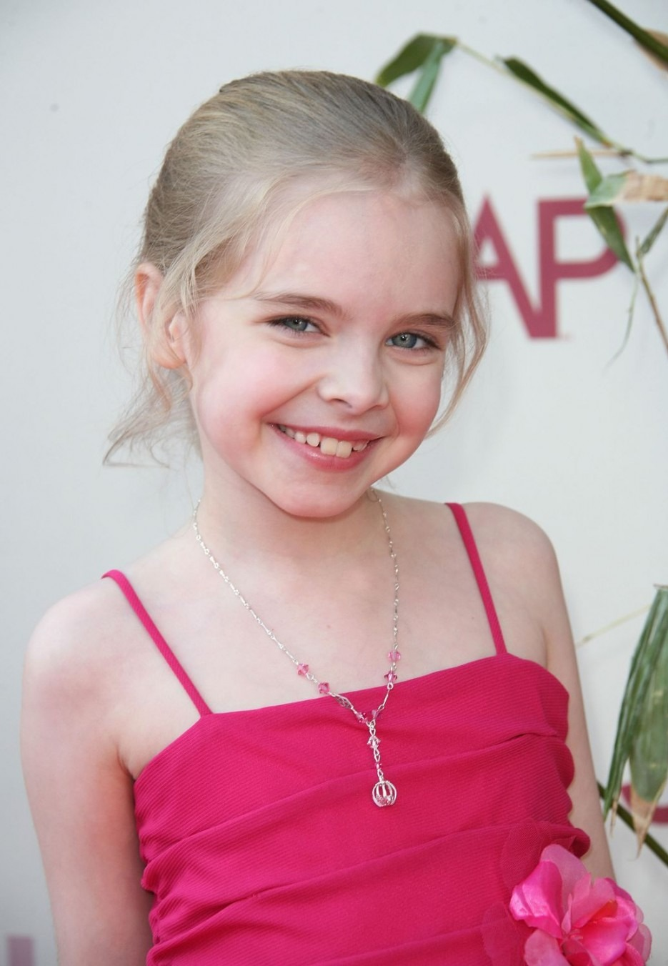 Young actress Darcy Rose is wearing pink dress and smiling in front of the camera.