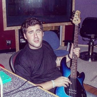A young Seth Firkins holding  an electric guitar