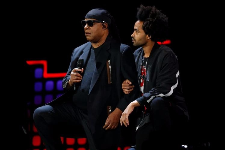 Stevie Wonder getting on his knee with his son, Kwame