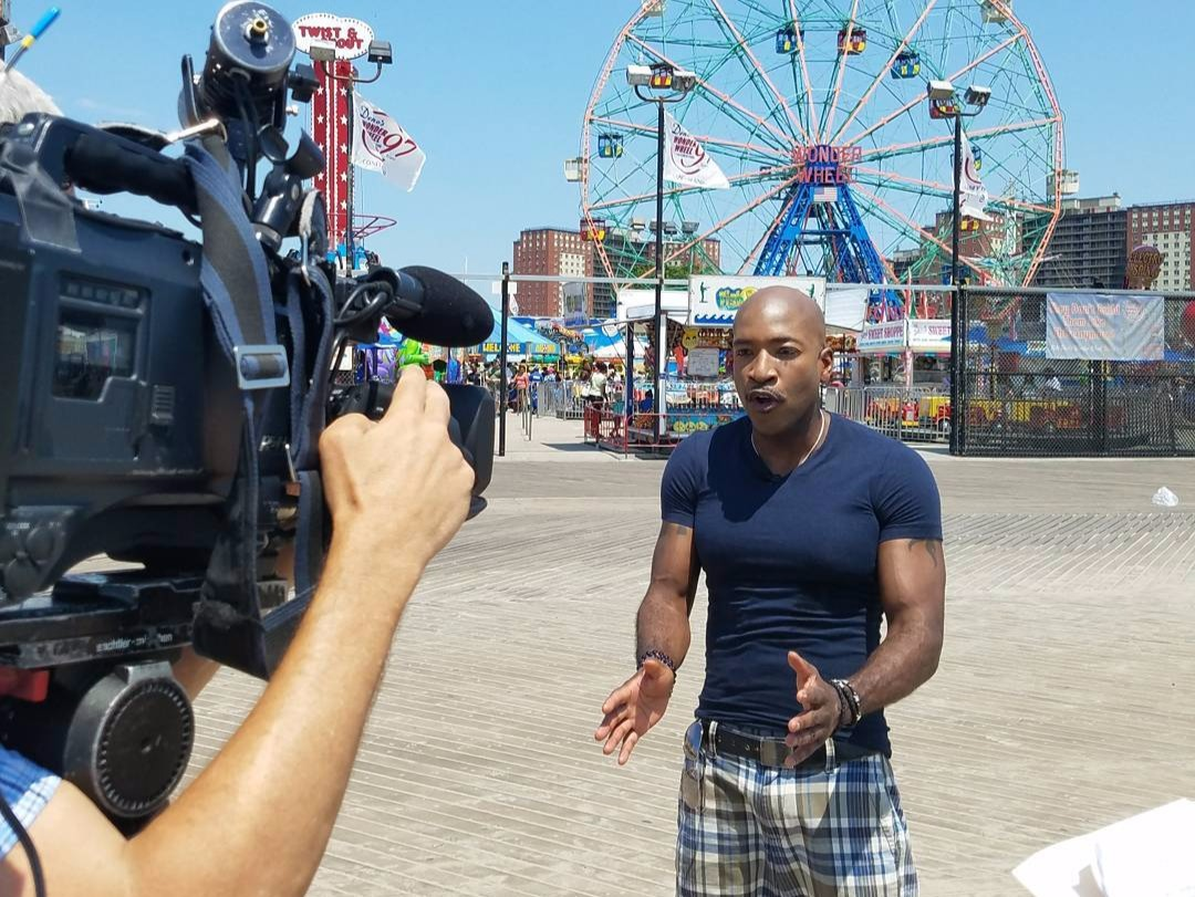 Antwan Lewis reporting infront of a camera, there is a ferris wheel behind him