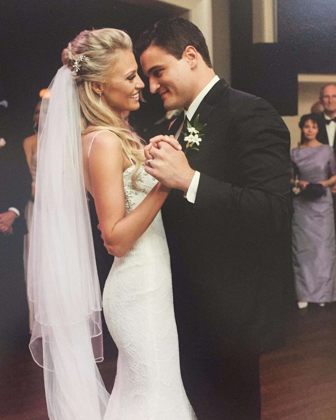 Carley Shimkus looks stunning in her wedding gown and she is smiling as her husband, Peter Buchignani give a glance at her