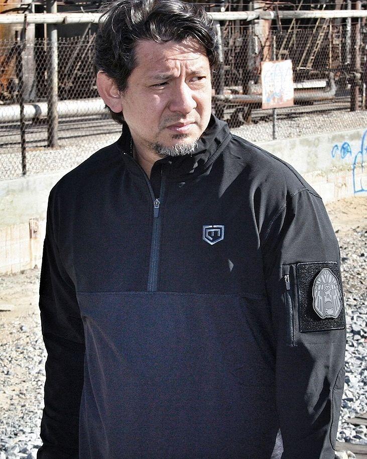 Doug Marcaida looking sideways wearing a black jacket.