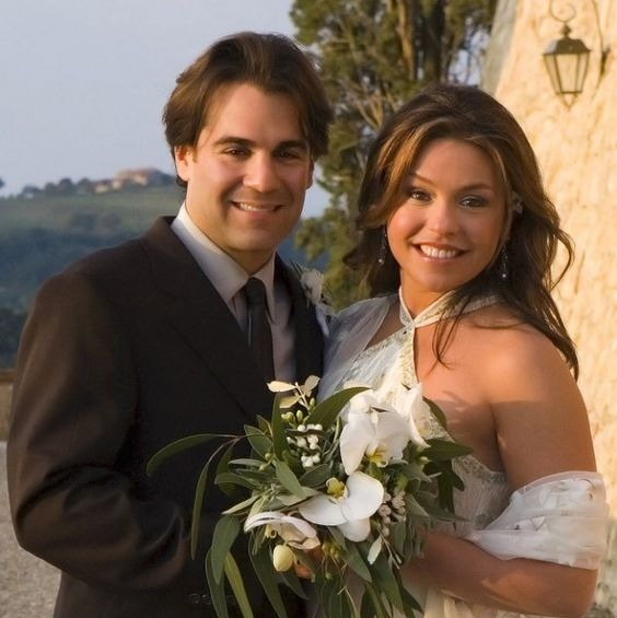 John Cusimano with his wife, Rachael Ray. The two are smiling for the camera. Rachael is holding flower on her left hand. The two are on their wedding dresses.