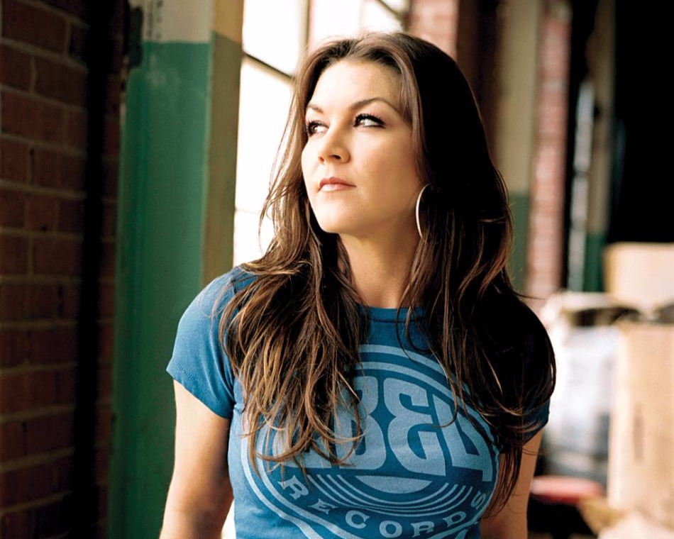 Gretchen Wilson wearing a blue t-shirt, she's looking to her top left