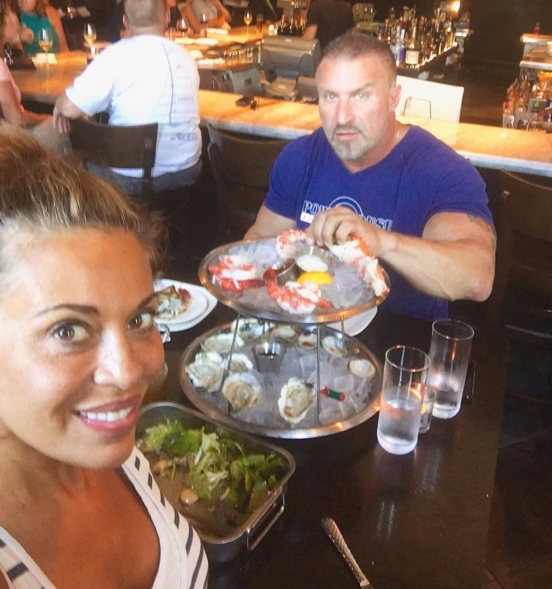 Dolores Catania is taking a selfie with her ex-husband Frank Catania. They are dining at a restaurant.