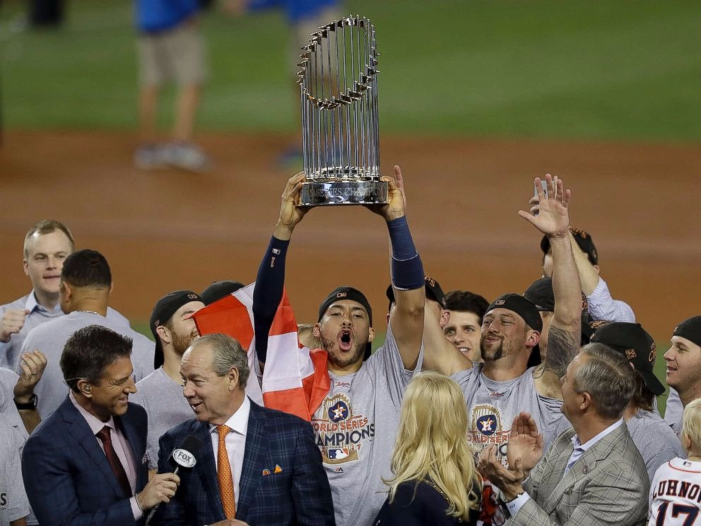 Houston Astros players celebrating win, Carlos Correa is holding the trophy