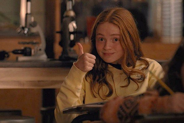 Sadie Sink portraying Mad Max in Stranger Things, she's giving the thumbs up, there are two microscopes behind her