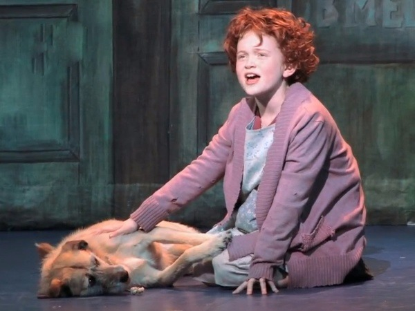 Sadie Sink standing in costume as Annie, there's a dog at her heels