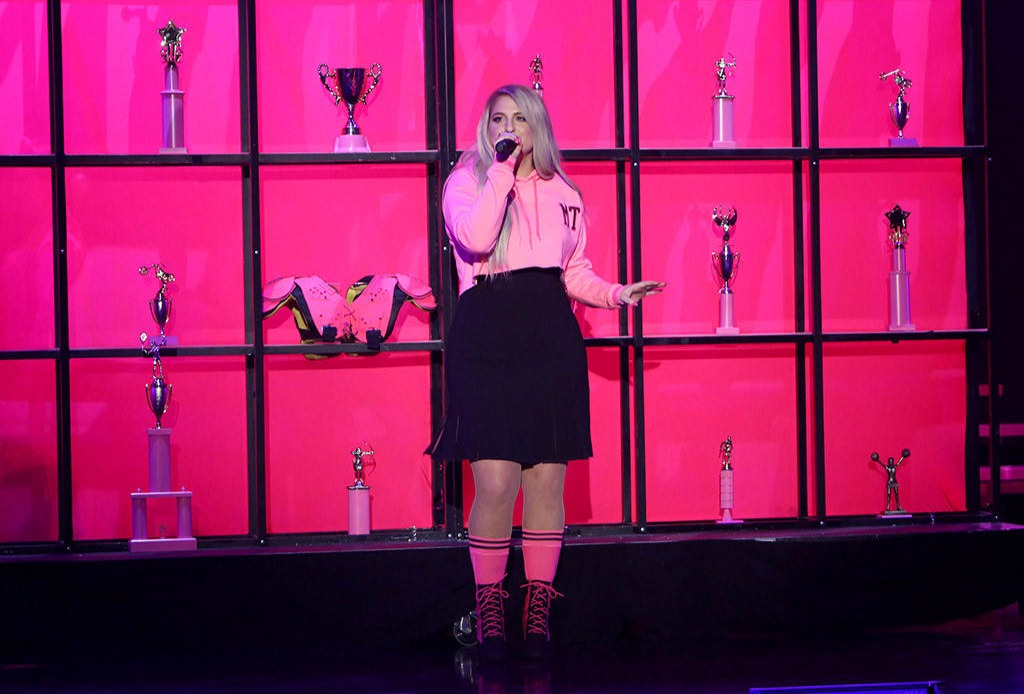 Meghan Trainor standing in the sets on The Ellen DeGeneres,  singing with a mic on her hand. She wears a pink hook and a black skirt.
