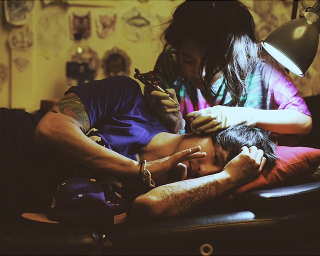 Julien Bam lying on his side as a tattoo artist holds up a tattoo pen next to his ear