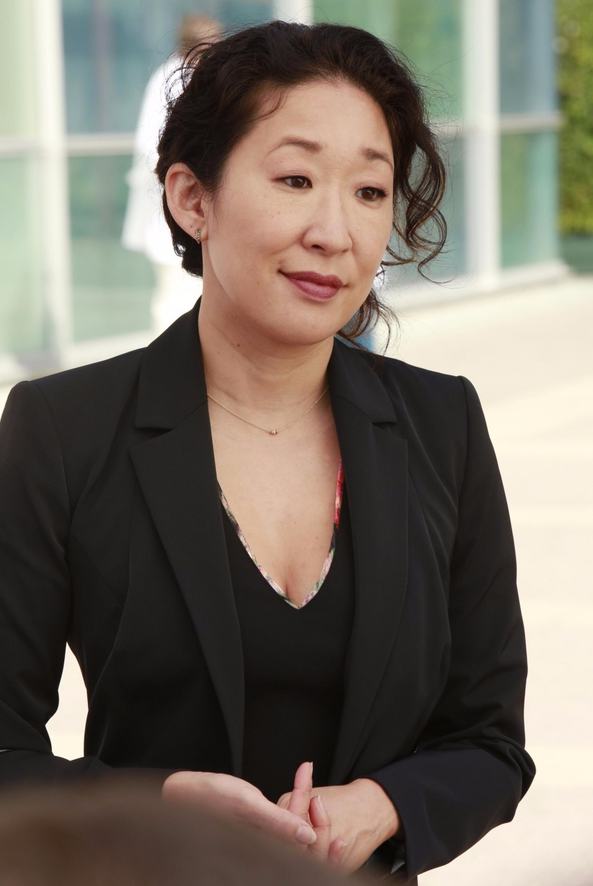 Sandra Oh gives a subtle smile, looking away from the camera. She is wearing a black top inside a black suit.