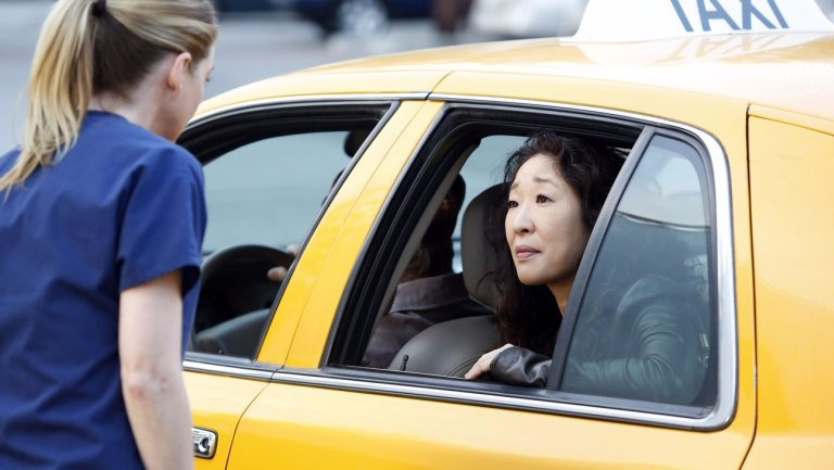 Meredith Grey (played by Ellen Pompeo) is standing outside a yellow cab with Cristina Yang (played by Sandra Oh). This was Cristina Yang's last appearance on Grey's Anatomy.