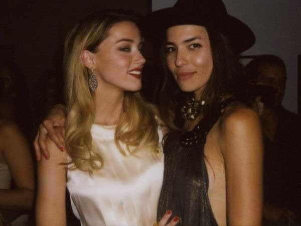 Tasya van Ree and her ex-girlfriend Amber Heard. They are attending a party. Tasya is wearing a backless black top with a black hat and Amber is wearing a off white turtle neck dress. They both are sticking close to each other, the photo was clicked when they were in relationship.
