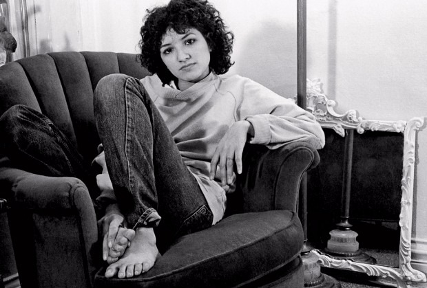 Young Sandra Cisneros had rather curly and short hair. She looks cool posing on a sofa.