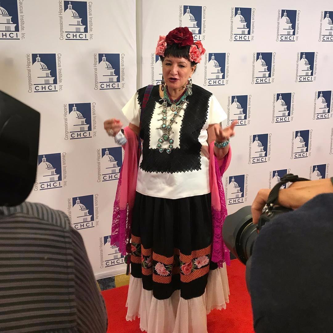 Sandra Cisneros walking the red carpet wearing an ethnic dress.