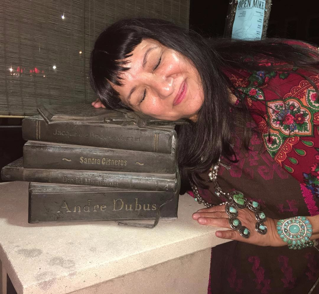 Sandra Cisneros is closing her eyes resting her head on her memorialized books in Iowa City monument.