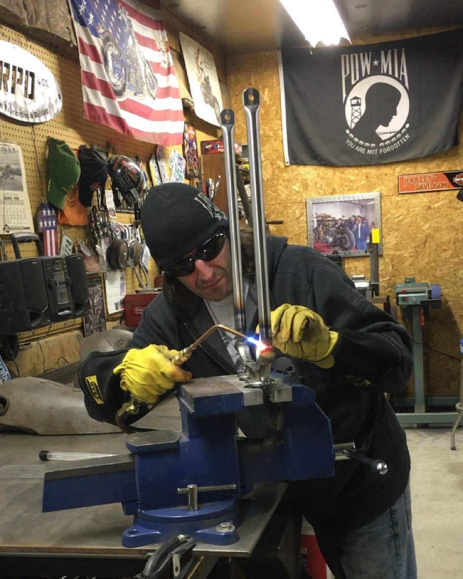 Rick Petko is welding a knuckle fork tube for his new racer.