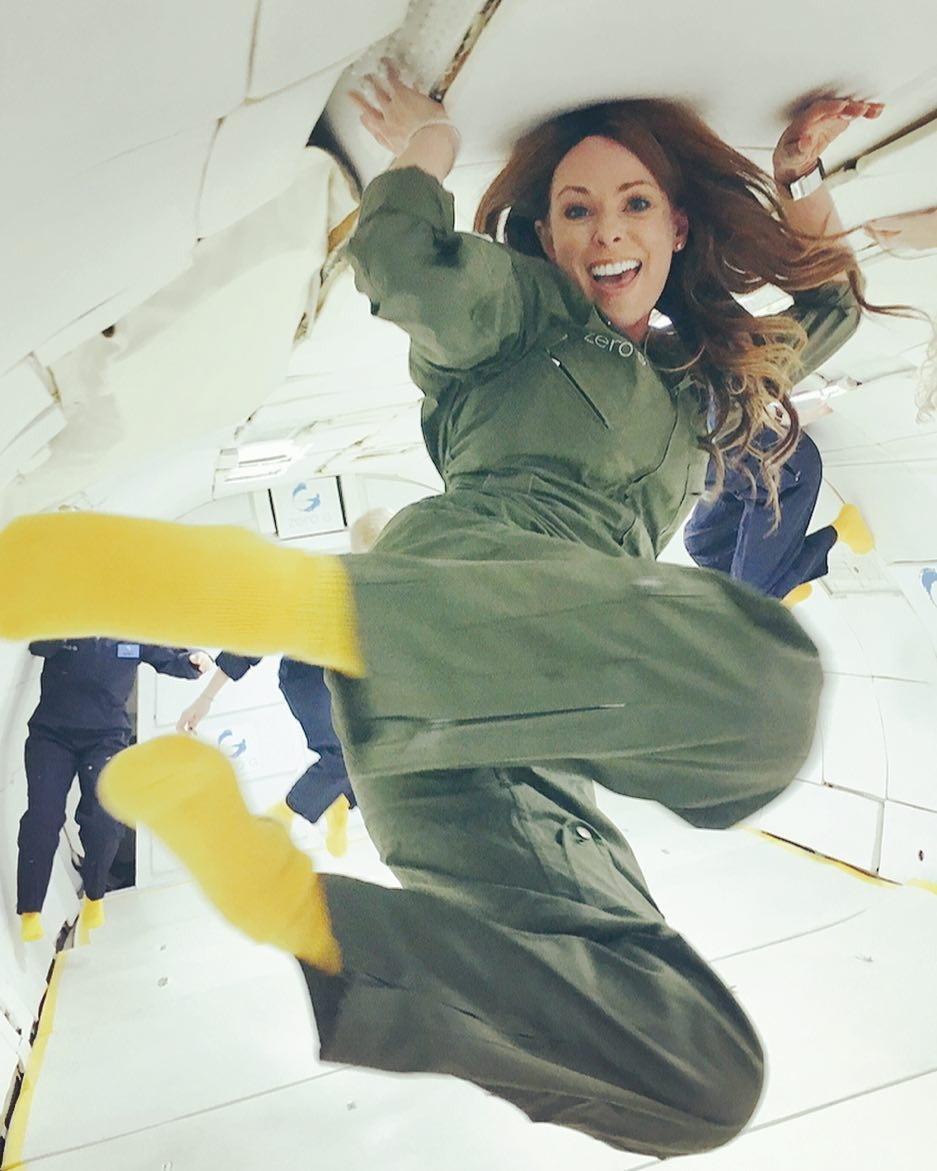 Amiko Kauderer experiencing the zero gravity. She is swirling in the air with a big smile on.