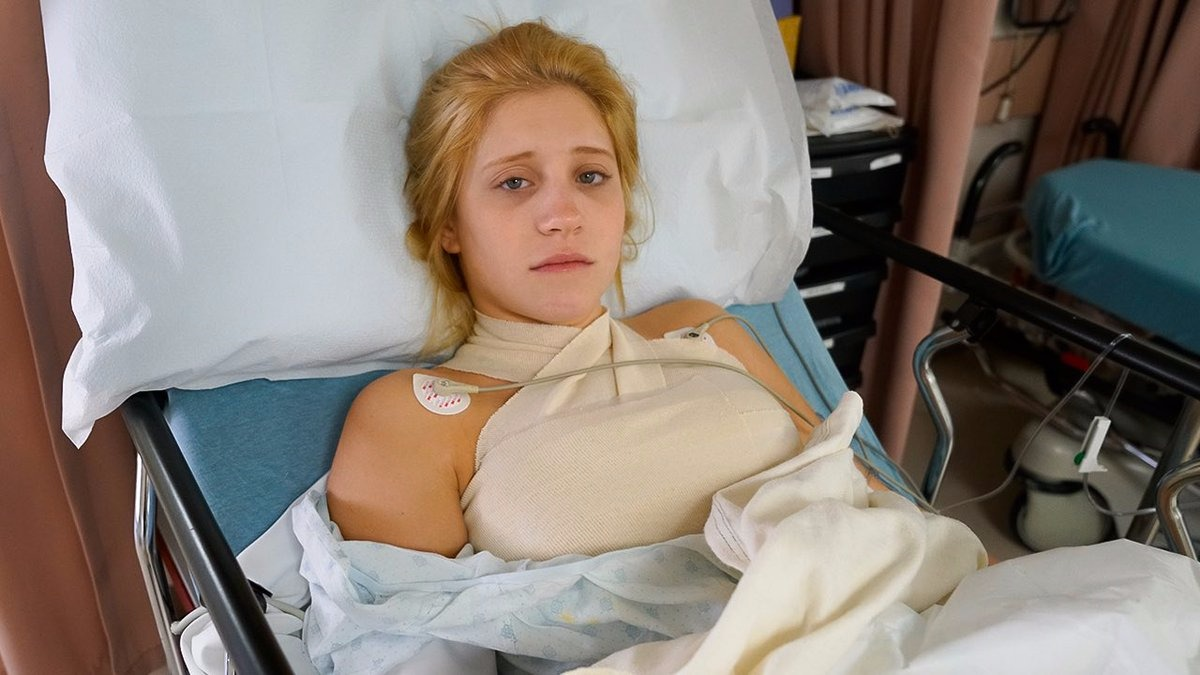 Lizzy Wurst looks like she is in pain after her breast implant procedure. She is lying in the hospital bed.