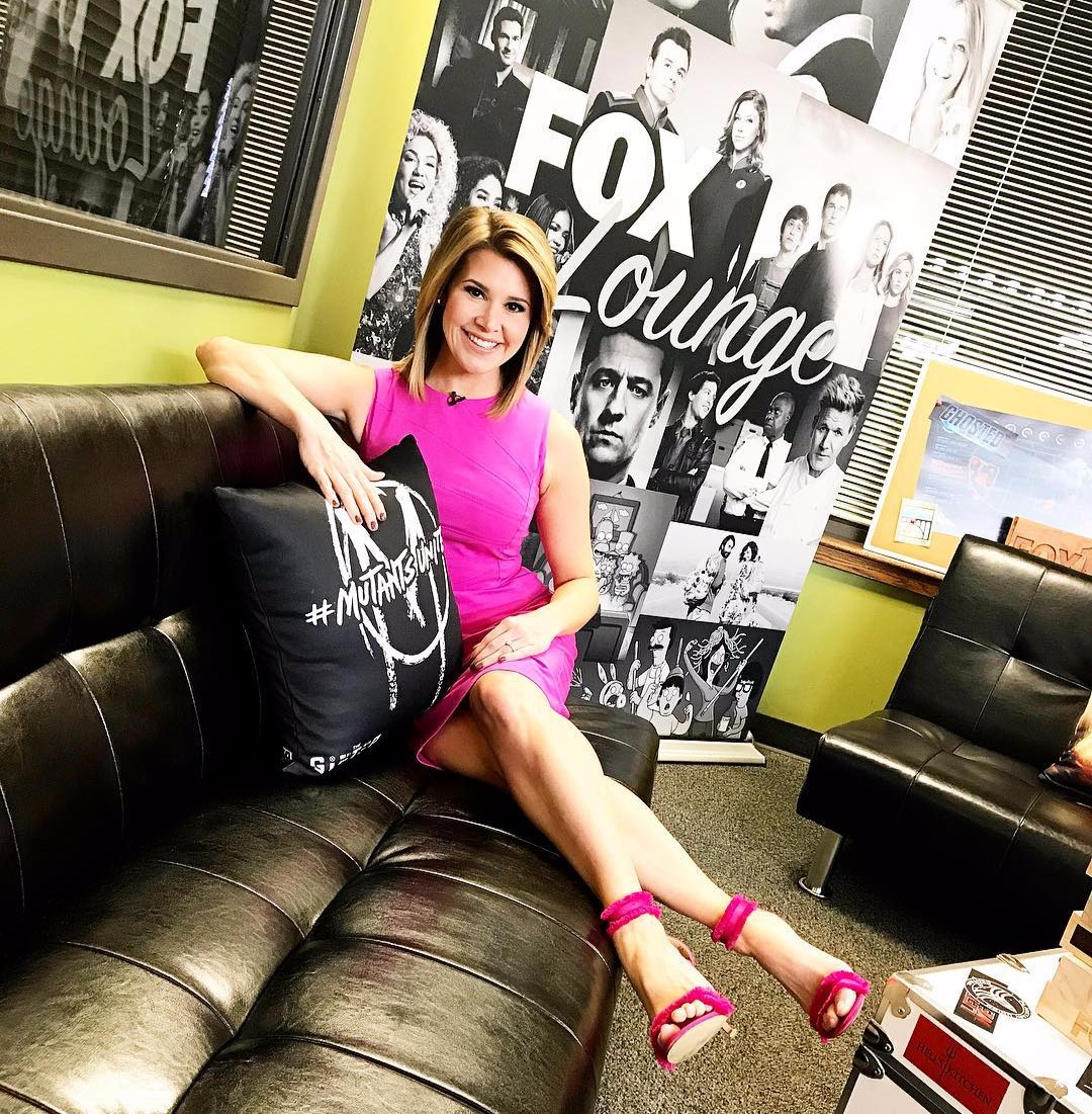 Kara Sewell sitting cross legged on a couch, there's a large poster behind her that says Fox Lounge