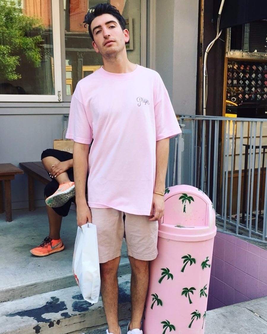 Beau Cassidy flaunting his pink outfit which matches the trash can beside him.