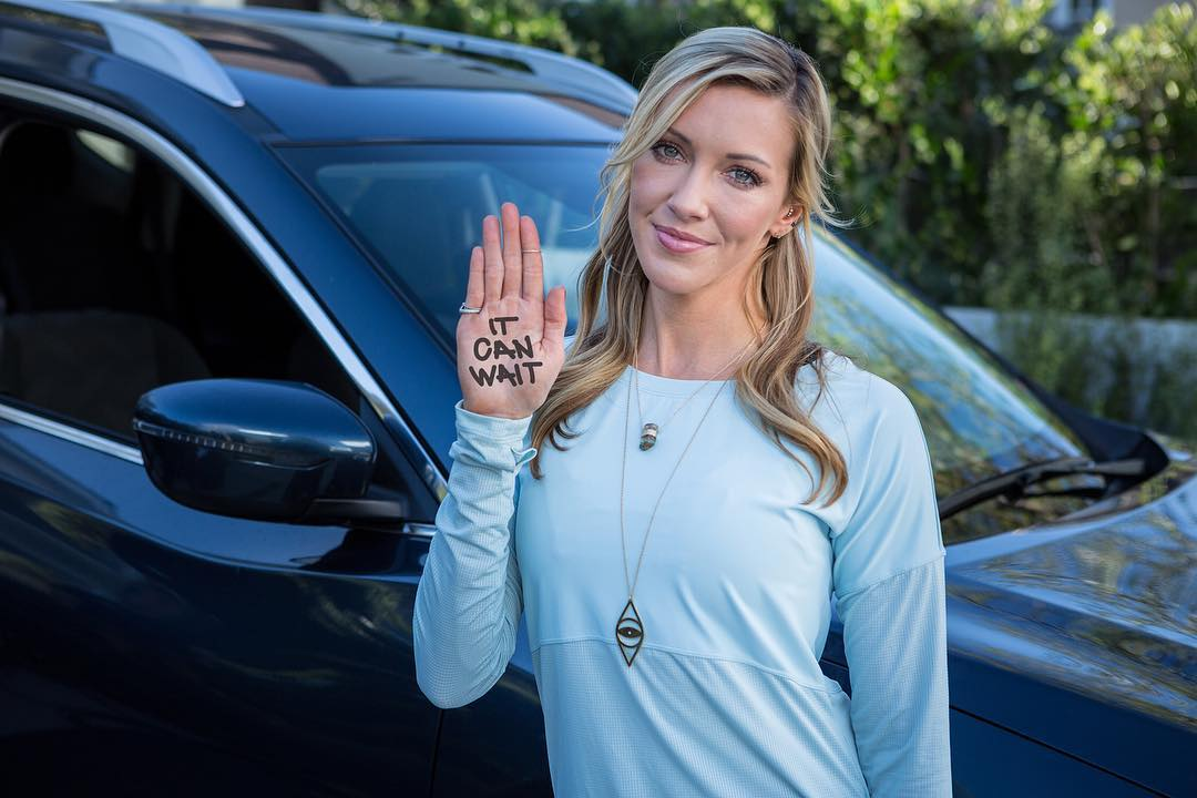 """Katie Cassidy raising her right hand up on which """"IT CAN WAIT"""" is written"""