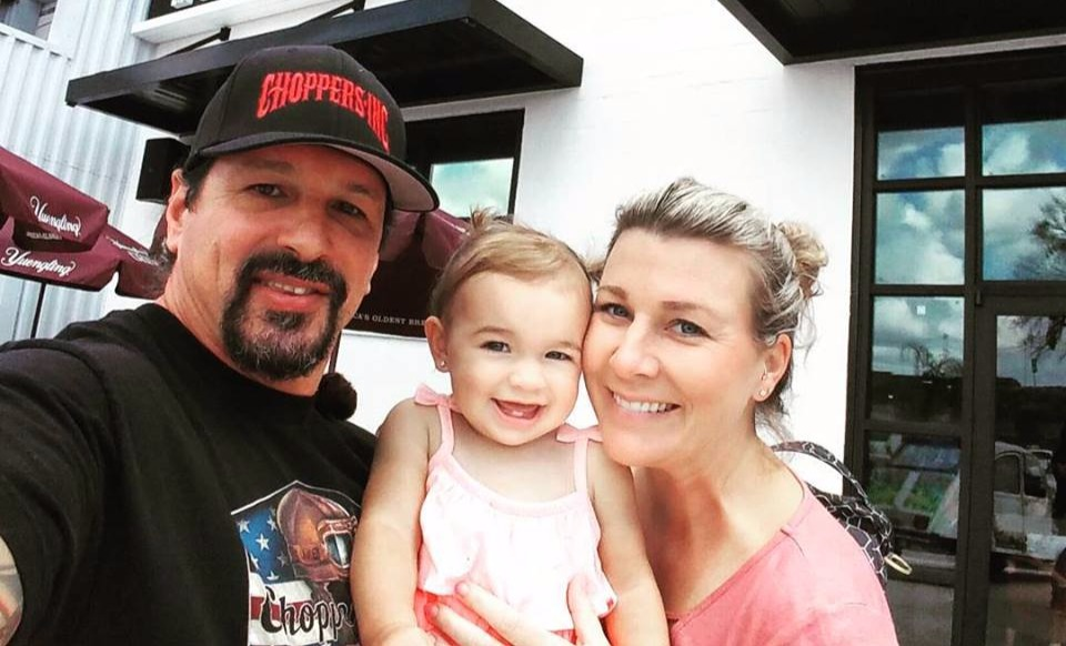 Billy Lane talking selfie with wife and first daughter infront of a cafe, Ace Cafe