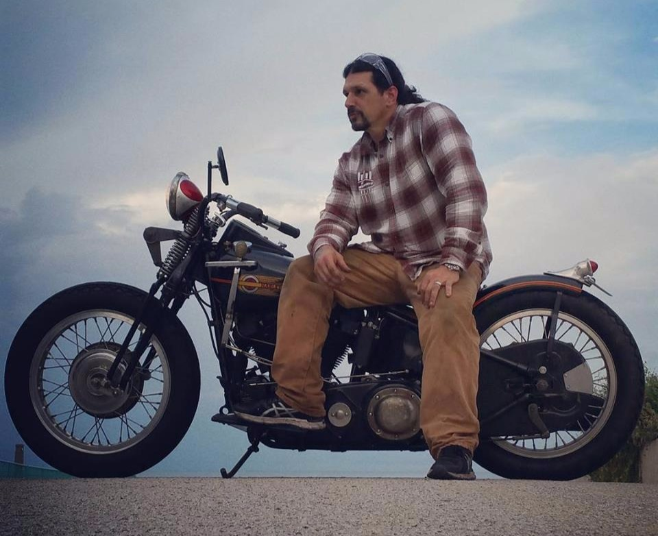Billy Lane of Choppers Inc. sitting sideways on a motorcycle.