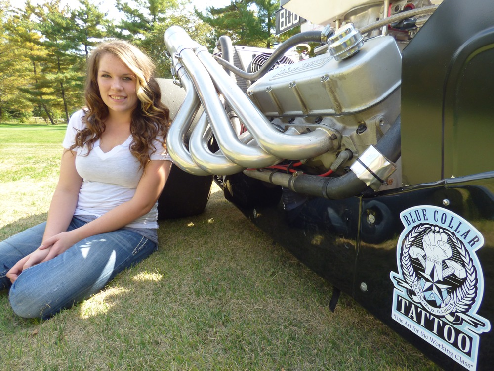 Jackie Braasch sitting on the grass, there's a huge set of car engine beside her