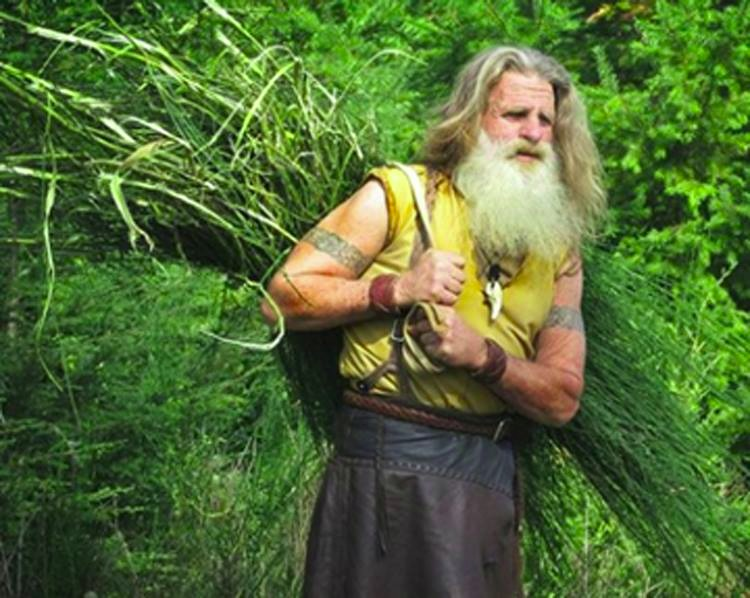 Mick Dodge carrying bundle of shrubs on his back. He has long and white hair and beard.