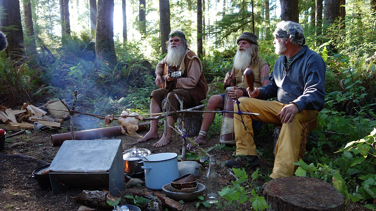 Mick Dodge playing Zimbabwean Traditional Drums,  while one  friend is holding a guitar and other is holding another music instrument. They all are sitting around the fire on the  wood log.