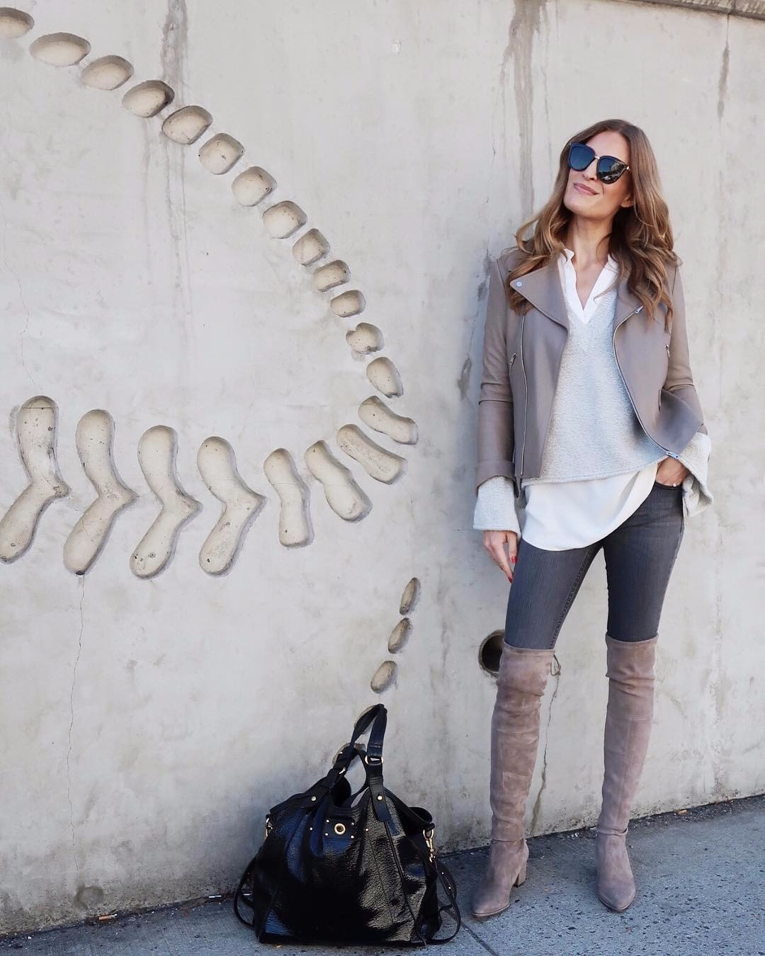 Laura Behnke is dressed up in all shades of gray from her coat to her boots. She has got a tall height and slim body. She is looking up with her sunglasses on.