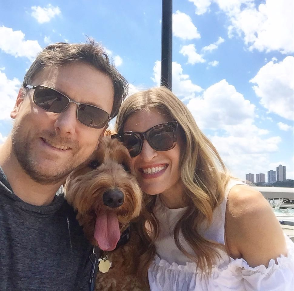 Laura Behnke and her fiance Marc Fowler out with their Labradoodle, Oxford. The three of them are in good mood. They are smiling as Marc takes the selfie in a sunny day.