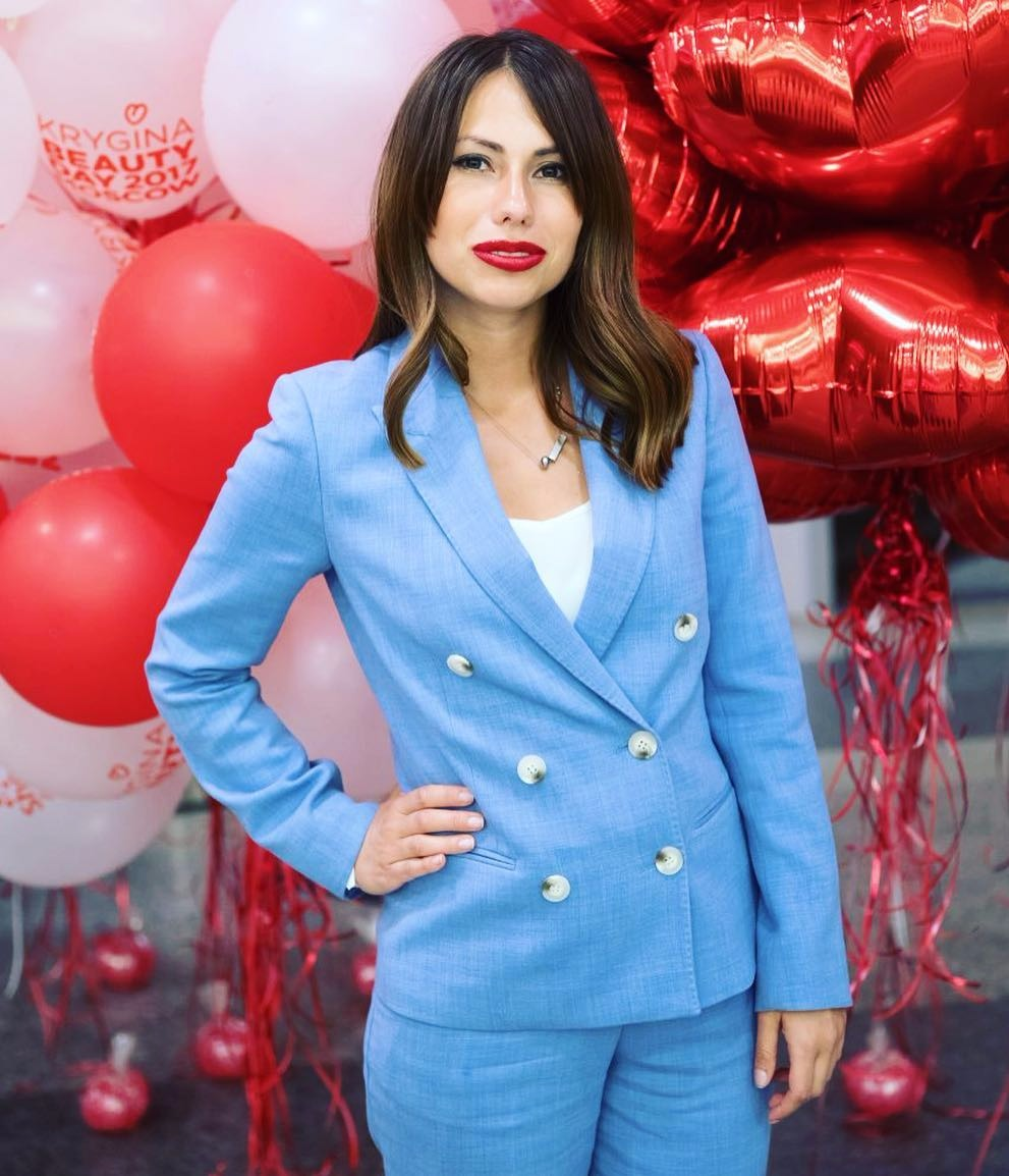 Maria Komandnaya with hands on her hips, there are balloons behind her