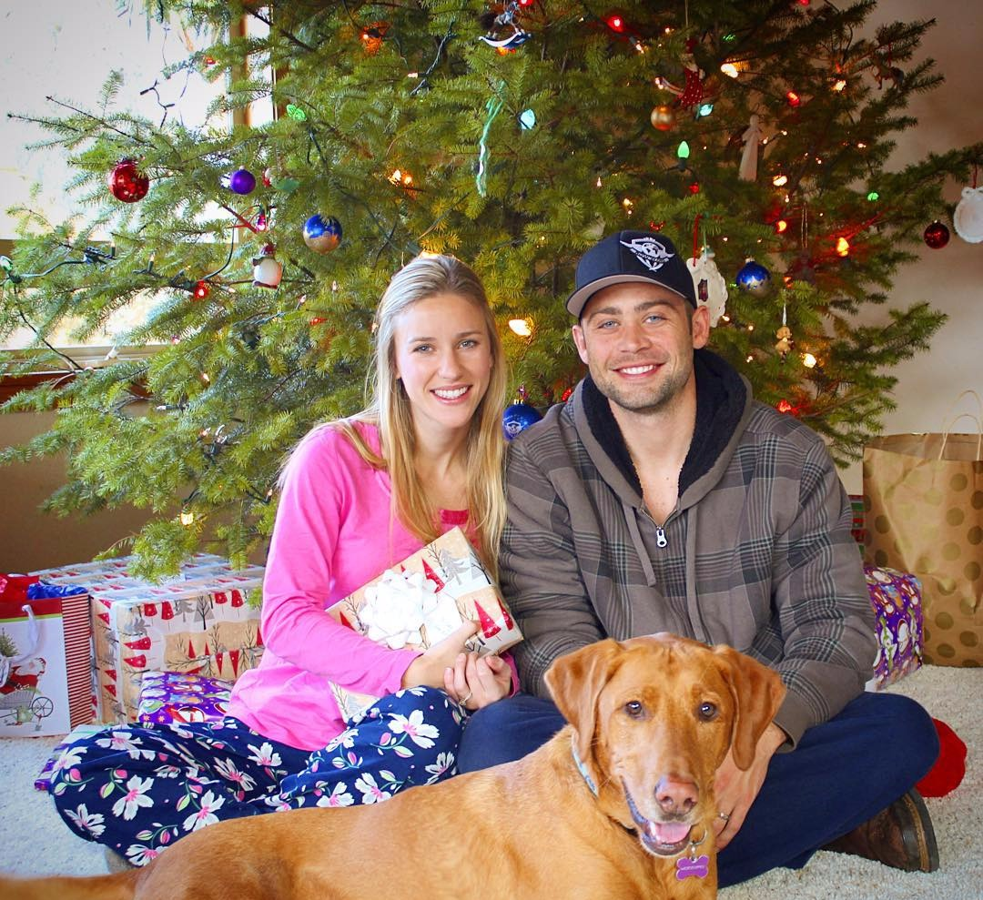 Felicia Walker and her husband Cody Walker sitting by their decorated Christmas tree. They are wearing casuals. They are both smiling while Felicia holds a Christmas present.