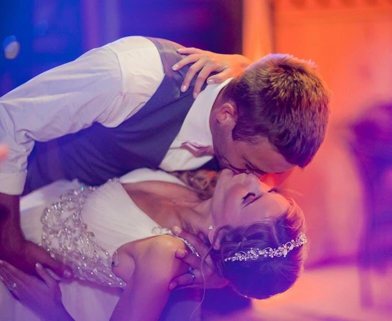 Felicia Walker and her husband Cody Walker on their wedding day. The bride and groom are in a lip lock position in their beautiful wedding gowns. Cody tilts her while he kisses her.