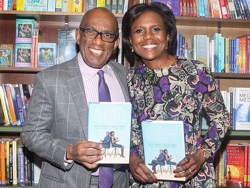 "Deborah and Al Roker are holding their co-written book ""Been There, Done That: Family Wisdom for Modern Times"" and showing it to the camera."